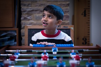 Boy playing table football lit my ambient light. Photographed by Anna Hindocha/Warm Glow Photo