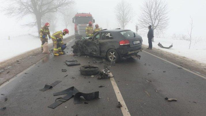na środki drogi rozbity samochód osobowy, wokół porozrzucane elementy pojazdu, przy samochodzie 4 strażaków dalej samochód ciężarowy