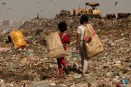 On the landfill there is every imaginable type of refuse, from kitchen scraps to animal parts, plastic, old film strips, broken ceramics, fabric. The diverse army of scavengers?billions of insects, a herd of cows, men, women and children?all move constantly toward the top of the pile with every new truck load. The pickers work the pile using home fashioned picks to move useless garbage aside in their hunt for anything reusable, recyclable, saleable?clothes, shoes, plastic, human hair...There is no such thing as a safety zone here. If you are talking to your friends, you are ripe for getting run over. Full attention is required?the dump trucks could bury you, the bulldozer could run over you, the pile, spongy and hollow in places, could consume you.