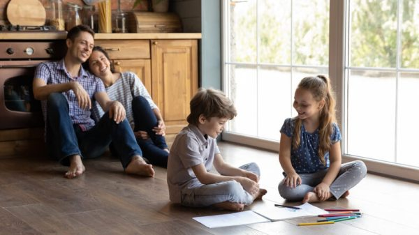 Happy family relaxing in kitchen while kids color and draw together.