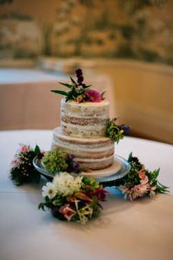 Lightly frosted two-tier wedding cake with farm fresh florals