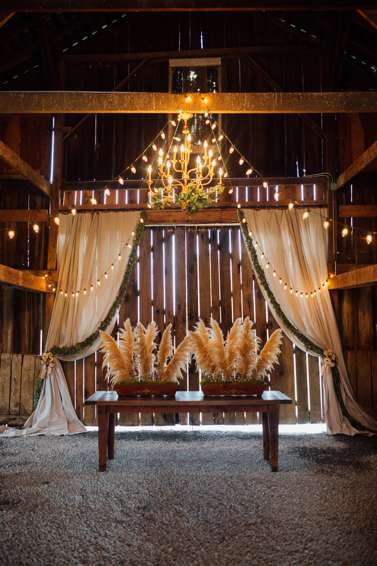 Warrenwood Barn Wedding Ceremony alter and greenery lined curtains