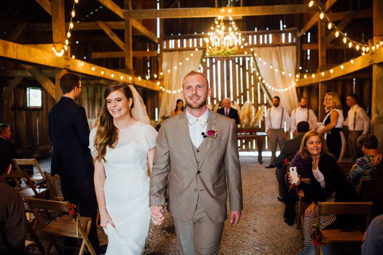 Bride and groom exit vintage rustic barn ceremony