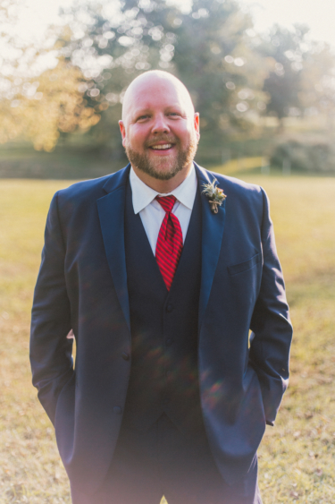 Groom dressed in navy suite and red tie with a succulent boutonniere