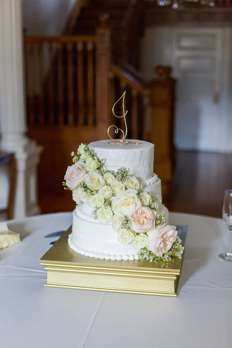 Ivory three-tier wedding cake with gold topper and cake stand with lots of flowers
