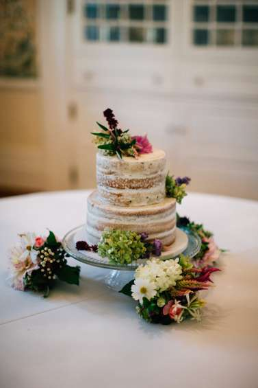 Two-tier naked layered wedding cake with farm fresh flowers