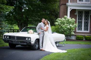 Bride and groom with vintage car in front of historic home