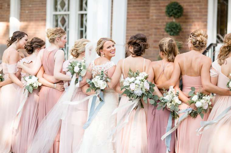 Blush flowy bridal party in front of venue with southern charm