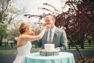 Bride and Groom cut the cake at outdoor wedding ceremony