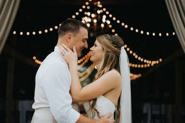 Portrait of Bride & Groom with string lights in background