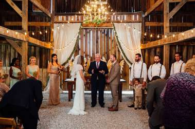 Barn Wedding Ceremony with drapery and chandeliers