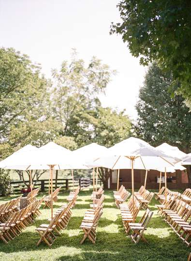 Umbrellas covering guests for an outdoor wedding ceremony