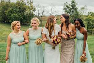 Seafoam and champagne bridesmaids dresses during fall outdoor wedding