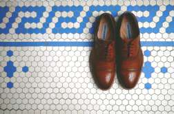 Brown leather shoes in blue and white tile bathroom