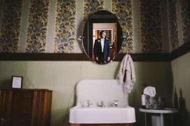 Groom in old style bathroom of Warrenwood Manor