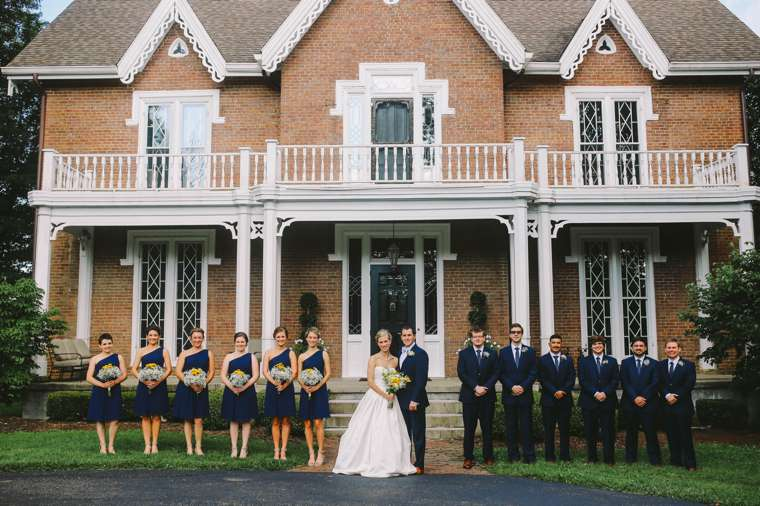 Wedding Party dressed in navy in front of old Kentucky mansion, summer farm wedding