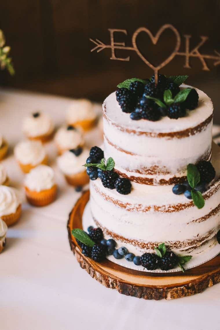 Ivory naked layered cake with blueberries and blackberries on a wood slab with a wood cake topper