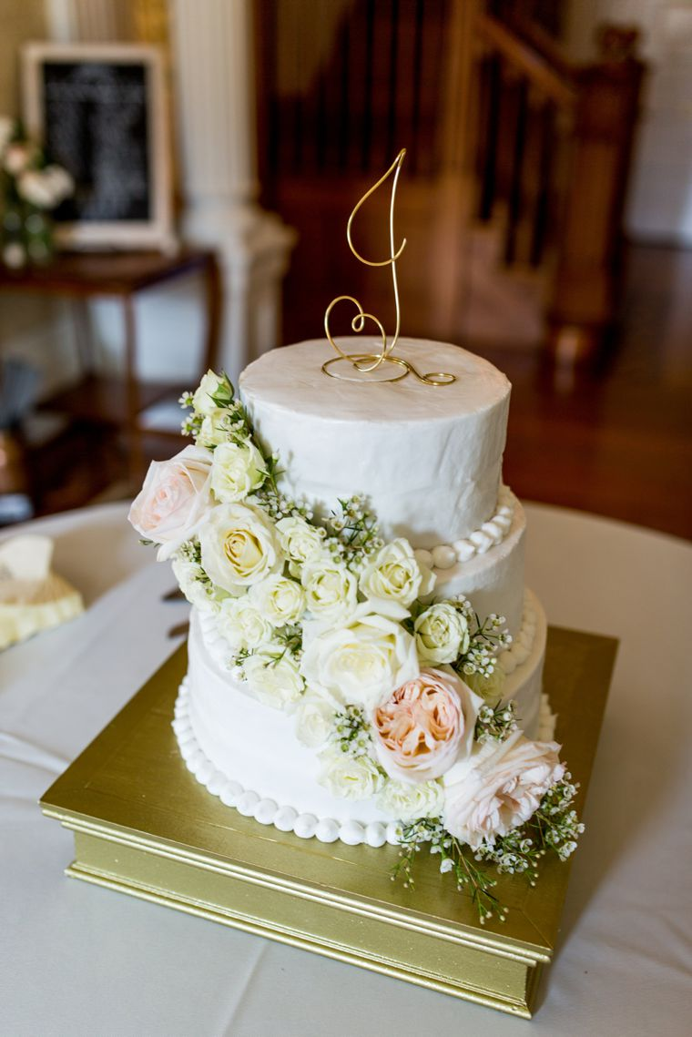 White cake with large roses and gold accents