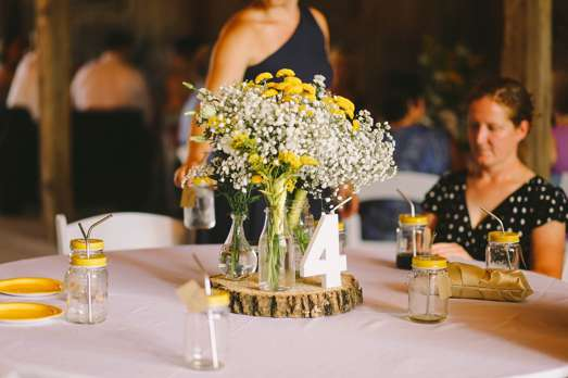 Rustic centerpiece, yellow and white flowers in jar on wood slice. Daring Tales of Darling Bones Photography.