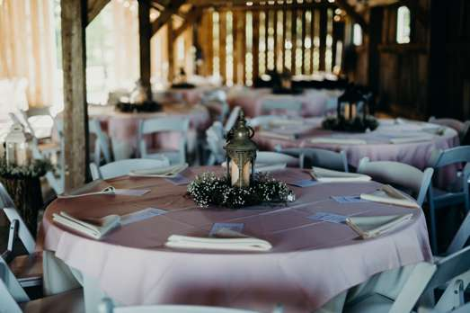 Light pink linens with lanterns and baby's breath centerpieces at traditional romantic wedding reception