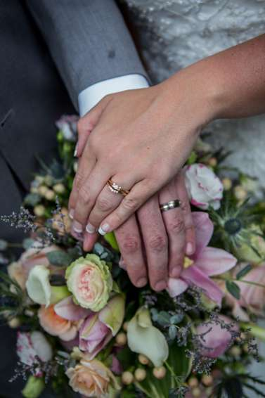 Wedding rings and bright bouquet at vibrant summer wedding