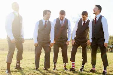 Groomsmen in grey blue suits and fun socks for rustic elegant Kentucky fall wedding