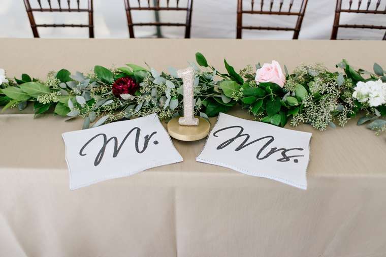 Head table with tectured accent linen, garland and signs