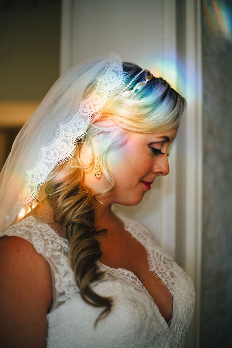 Fine art style bridal portrait with moody rainbows in historic home