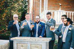 Groomsmen share a drink before fall wedding