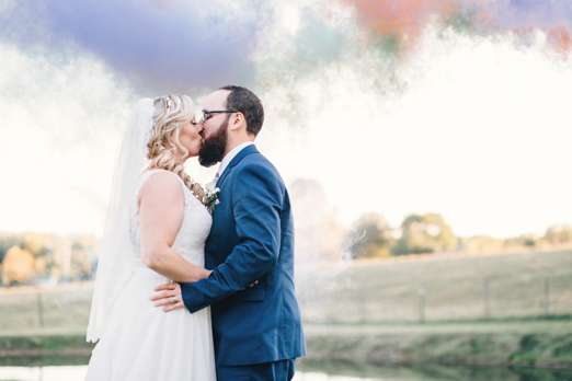 Couple's portrait with multi-color smoke bombs