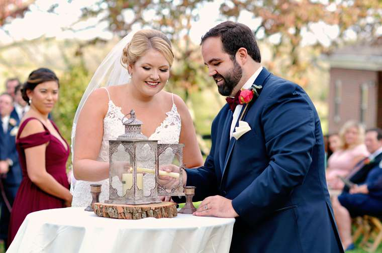 Bride and Groom light unity candle during fall outdoor ceremony