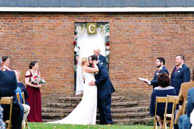 Bride and Groom kiss during fall outdoor ceremony