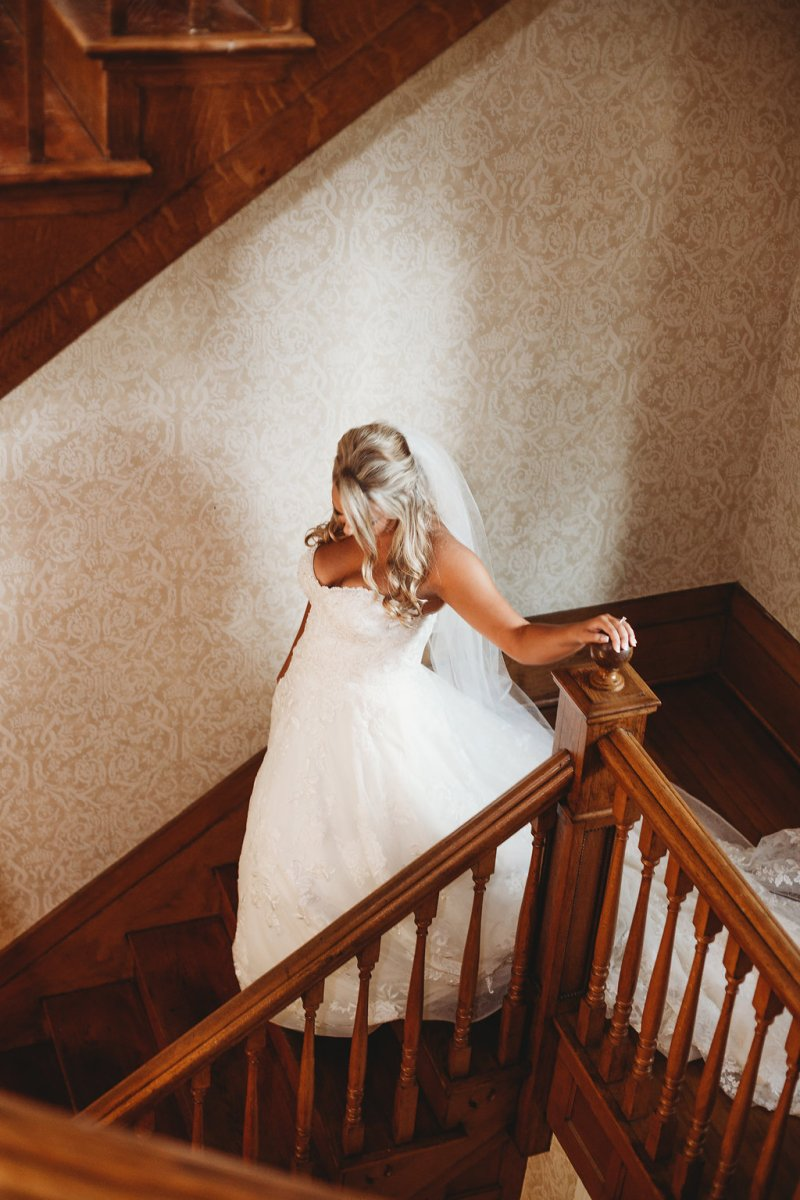 Bride going down stairs at Warrenwood Manor