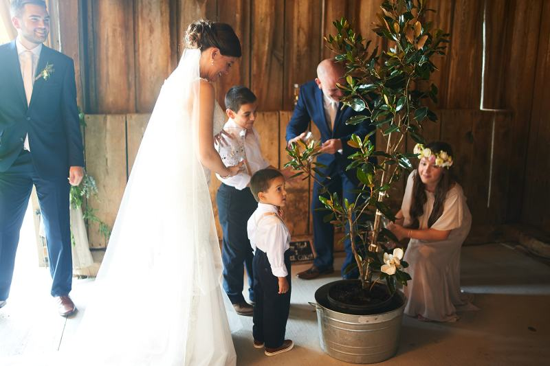 Tree planting ceremony to unify a family with kids during wedding ceremony
