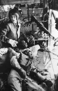 A mortally wounded comrade at his feet, Lance Cpl. James C. Farley, helicopter crew chief, yells to his pilot while in flight after a firefight in Vietnam, 1965.