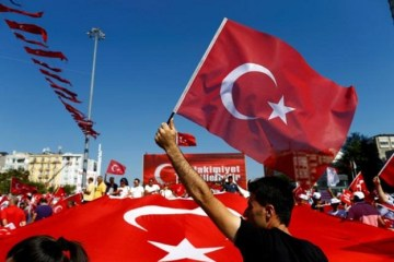 A man waves Turkey's national flag as supporters of various political parties gather in Istanbul's Taksim Square before the Republic and Democracy Rally organised by main opposition Republican People's Party (CHP), Turkey, July 24, 2016.  REUTERS/Osman Orsal