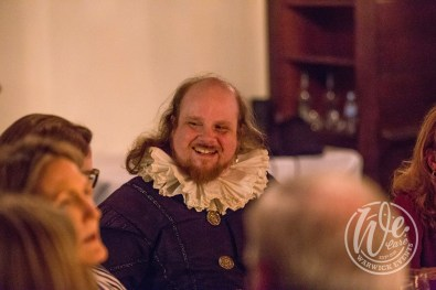 William Shakespeare actor at dinner laughing with guests