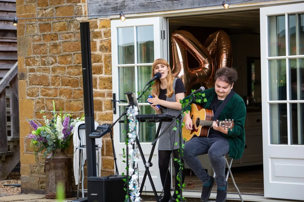 Female singer and male guitarist playing in front of patio doors at rustic-chic party