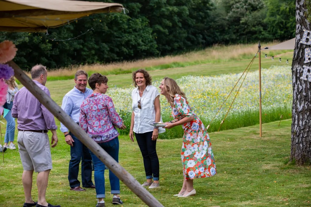 Birthday birl receiving gift from guests, tipi in foreground, flower meadow in background