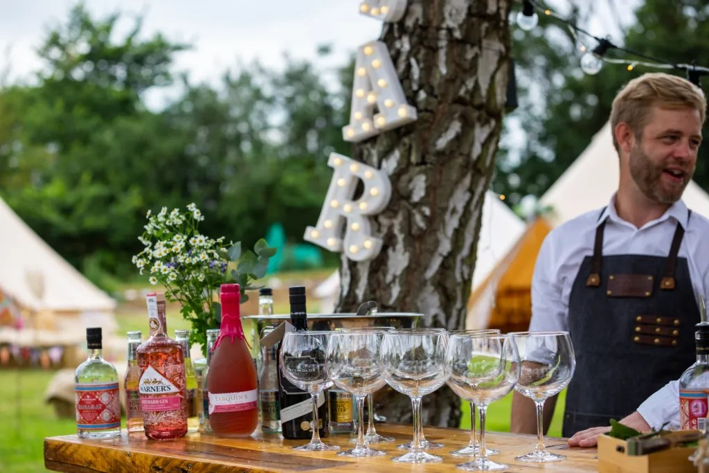 Popup cocktail bar decorated with wild flowers and lit up BAR sign hanging from tree