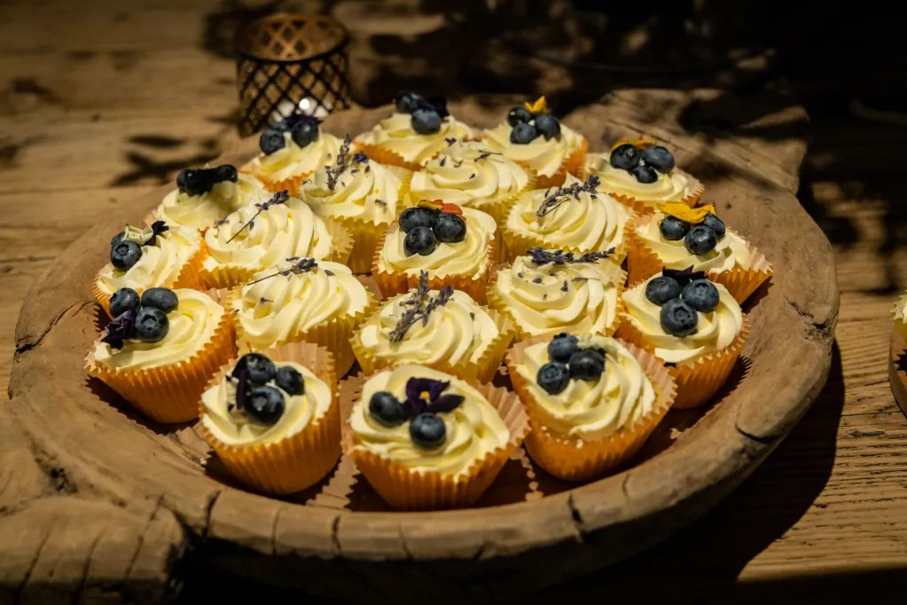 Cup cakes decorated with blueberries, edible flowers and lavender at rustic-chic party