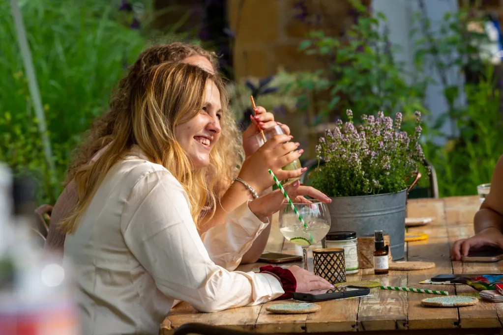 People smiling enjoying cocktails sat at trestle table with herbs in background