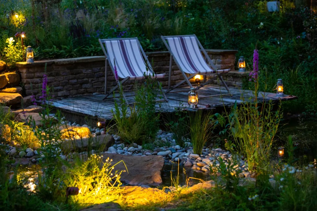 Deckchairs in late evening light, garden lit with lights and lanterns for rustic-chic party