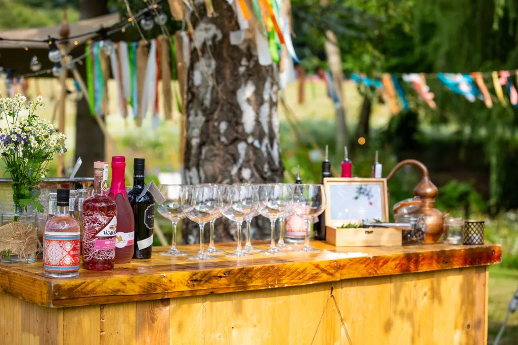 Popup cocktail bar decorated with wild flowers and ribbon bunting in background