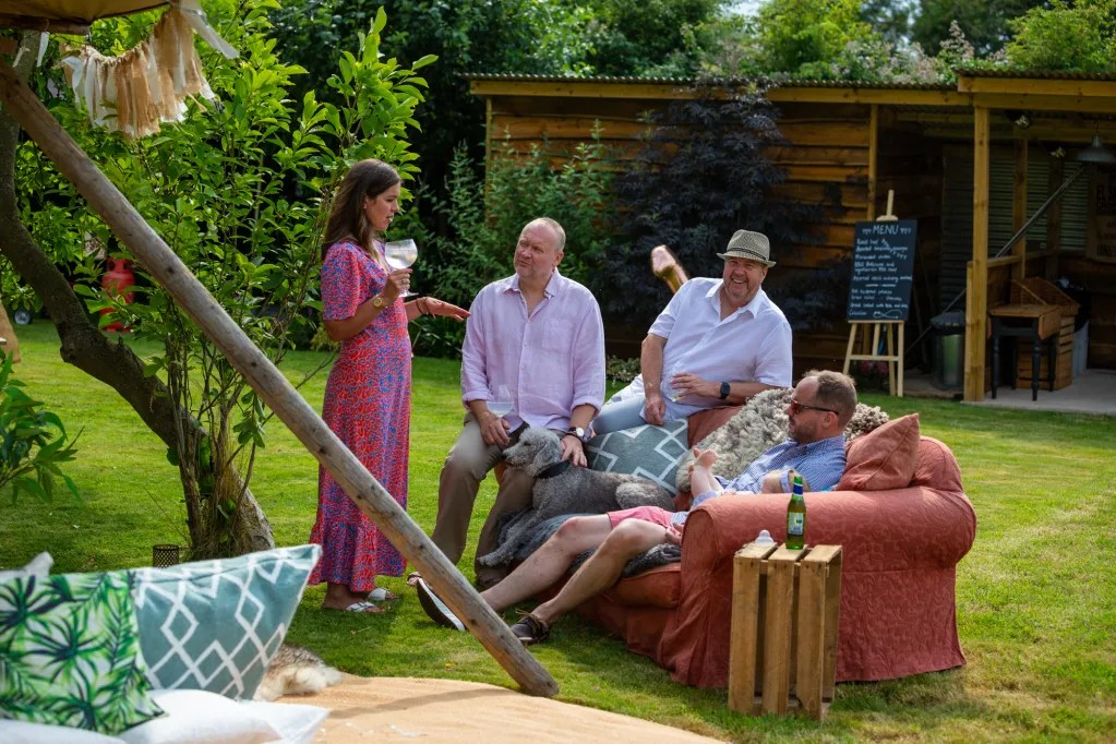 People relaxing on sofa outside, tipi and ribbon bunting in foreground