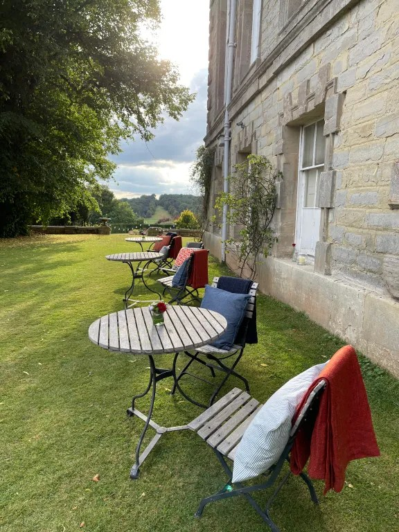 Bistro style tables in grounds of stately home for guests at VIP hospitality event