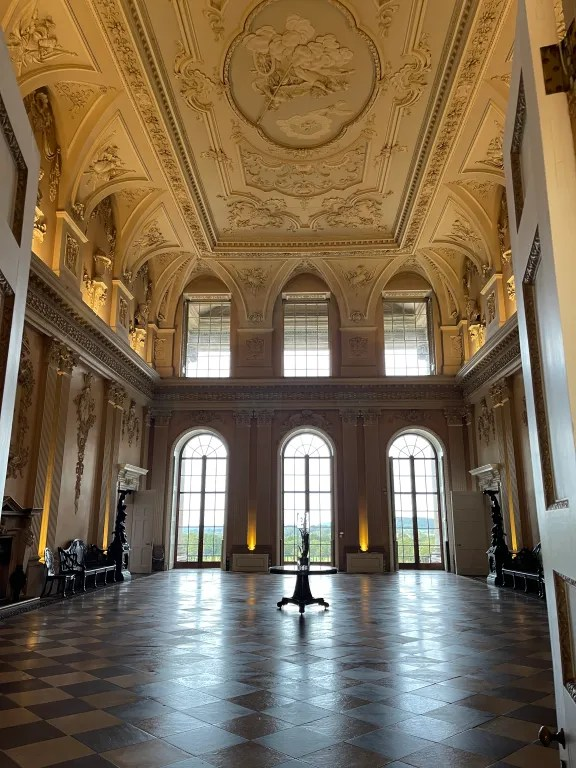 Ornate ceiling, large windows and stone floor of stately home great hall