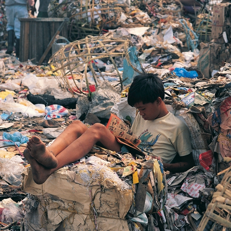 Boy surrounded by rubbish in landfill site