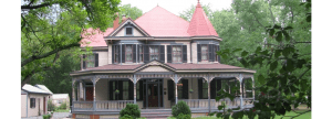 Red metal roof on restored Victorian house with wrap-around porch and many windows with dark green shutters