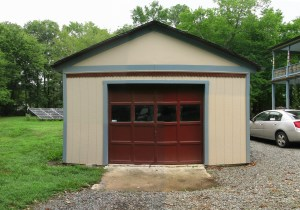 Front of garage shows dark red door, beige painted walls and blue trim with gravel driveway in front and between the garage and house